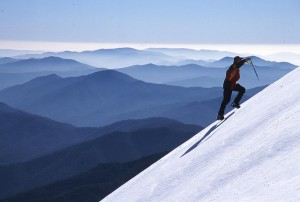Guy climbing snowy mountain