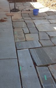 flagstones up close with painters tape marking the ones that need to be leveled