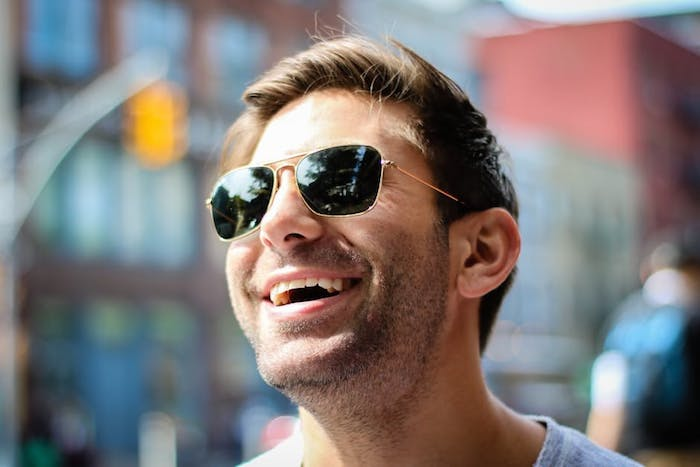 man-with-sunglasses-face-looking-up-at-sun-looking-youthful