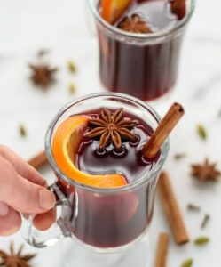 spieced mulled wine glasses with cinnamon sticks and orange peels as garnish