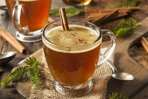 glass of hot butter rum with cinnamon stick
