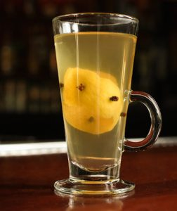 glass of hot toddy holiday cocktail with lemon and clove