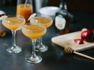coupe glasses with spiked apple cider holiday cocktail and apple garnish