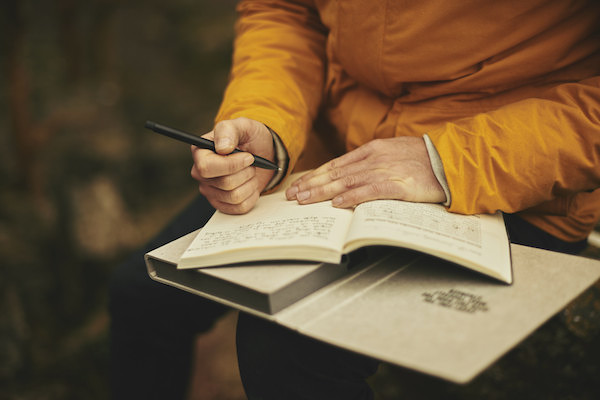 man journaling outdoors to help focus