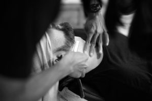 Barber giving a traditional shave with a straight razor