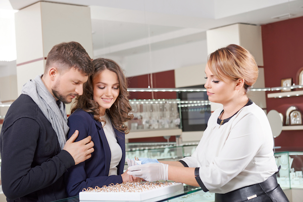 man and woman shopping for wedding bands in jewelry store