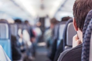 man sitting in aisle on night flight