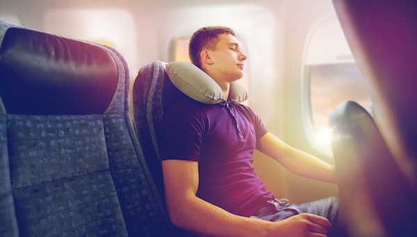 man sleeping in window seat with neck pillow on night flight