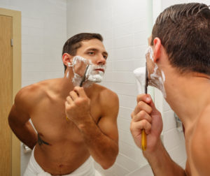 man wet shaving with traditional straight razor