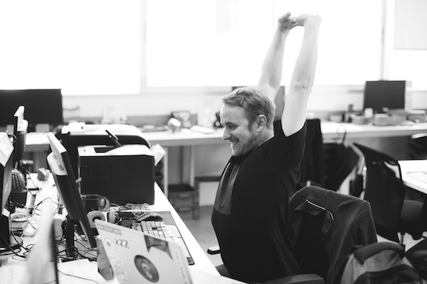 man stretching at desk during a break at work