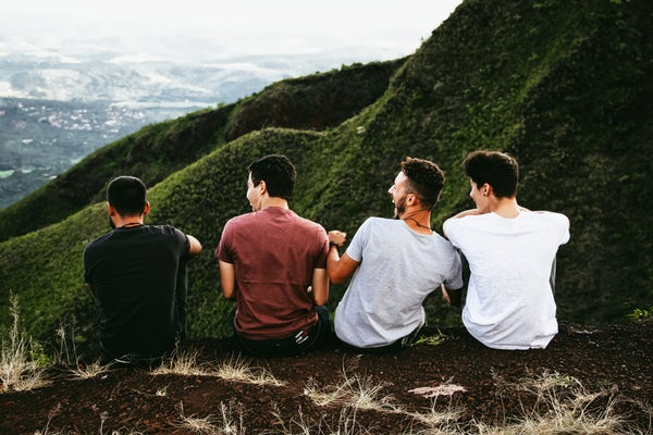 four men enjoying their annual guys trip on a mountain trail
