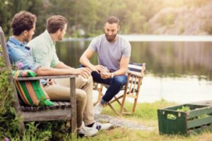 men talking next to a lake on their annual guy's trip
