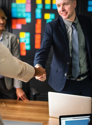 well-dressed man shaking hands with colleague