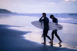 men walking together on beach with surfboards