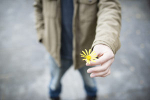 man holding out a flower